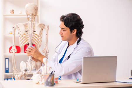 Young male doctor with skeleton