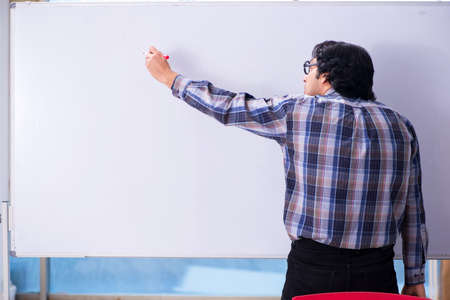 Funny male teacher in front of whiteboard Imagens