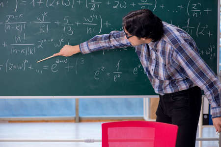 Young funny math teacher in front of chalkboard Imagens