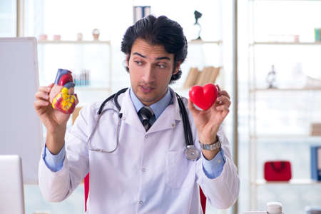 Young handsome doctor cardiologist in front of whiteboard Standard-Bild