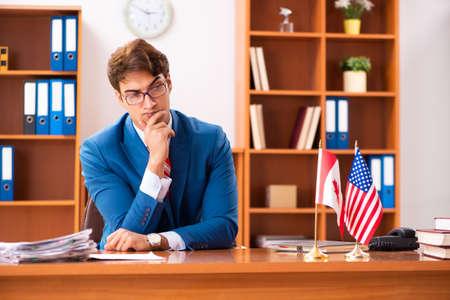 Junger gutaussehender Politiker, der im Büro sitzt Standard-Bild