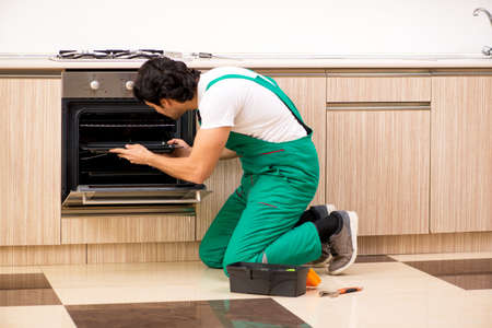 Young contractor repairing oven in kitchen Archivio Fotografico