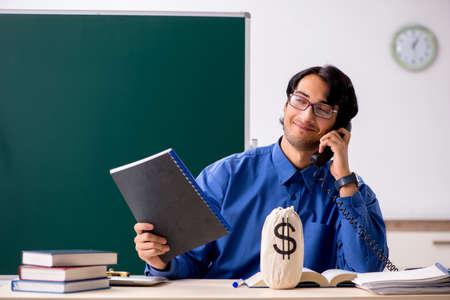 Young male teacher in front of chalkboard Zdjęcie Seryjne