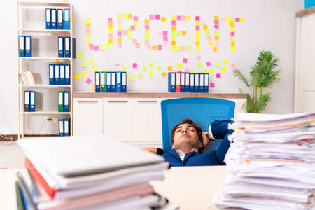 Young employee suffering from excessive work Imagens