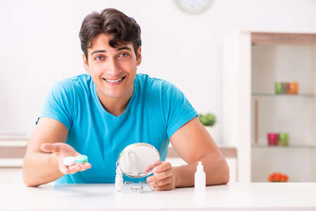 Man trying contact lenses at home Stock Photo