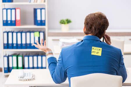 Office prank with kick me message on sticky note 스톡 콘텐츠