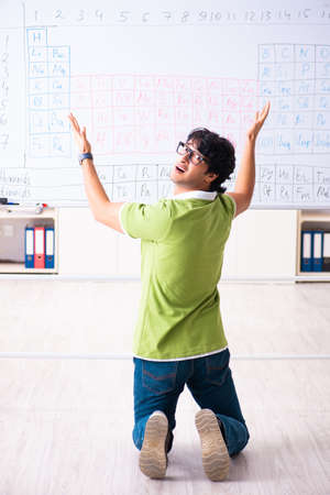 Young male student chemist in front of periodic table