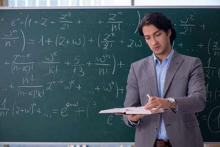Giovane bello insegnante di matematica in classe