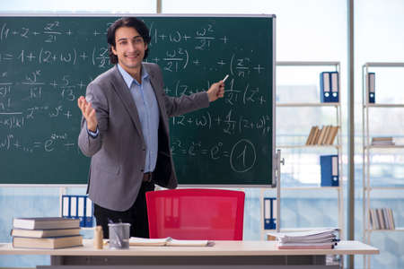 Young handsome math teacher in classroom