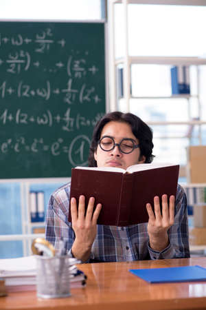 Young funny math teacher in front of chalkboard Stok Fotoğraf