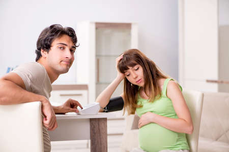 Husband checking pregnant wifes blood pressure Stock Photo