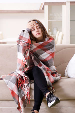 Sick young woman suffering at home Stock Photo