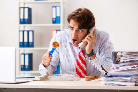 Man having meal at work during break Banco de Imagens