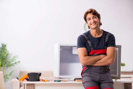 Young handsome contractor repairing fridge Reklamní fotografie