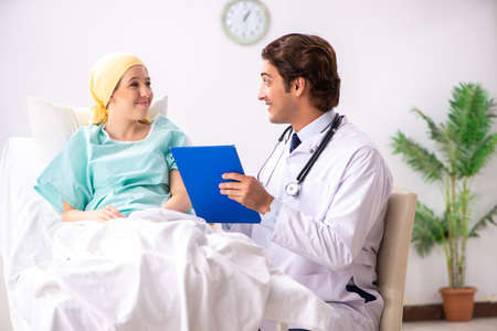Young handsome doctor visiting female oncology patient