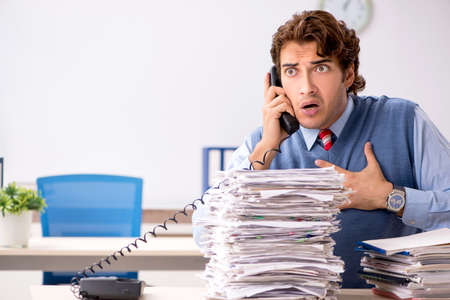 Young handsome employee unhappy with excessive work Stock Photo