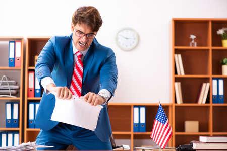 Junger gutaussehender Politiker, der im Büro sitzt