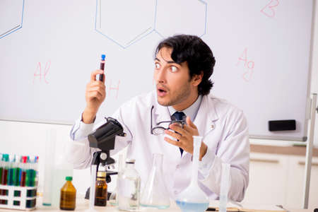 Young funny chemist in front of white board Stockfoto