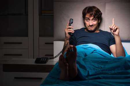 Young man talking on phone in bed Stock Photo