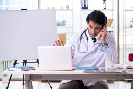 Young handsome doctor in front of whiteboard Stock Photo