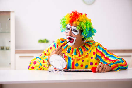 Male clown preparing for perfomance at home Stockfoto