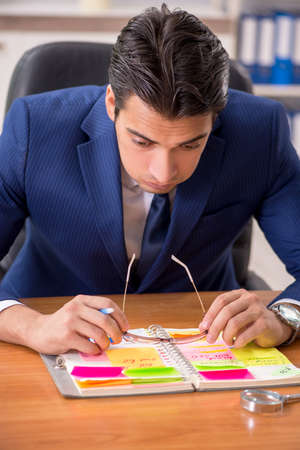 Young handsome employee planning his work activity Stock Photo
