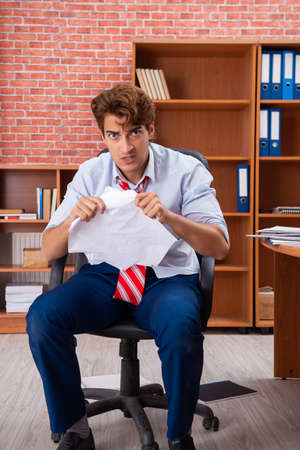 Unhappy businessman sitting in the office