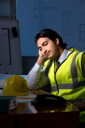 Young construction architect working on project at night 免版税图像