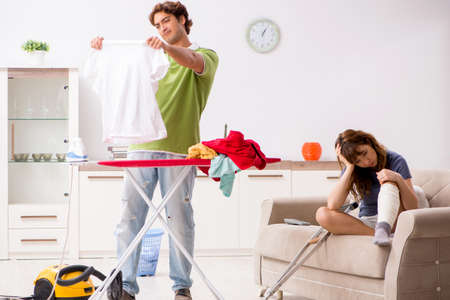 Husband helping leg injured wife in housework