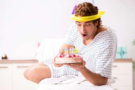 Jonge man viert zijn verjaardag in het ziekenhuis Stockfoto
