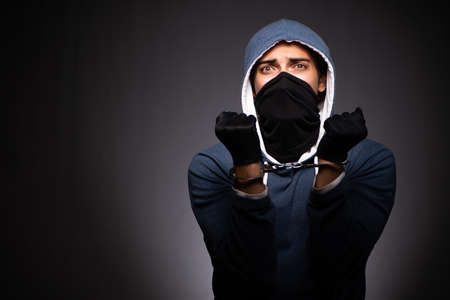 Young gangster in hood on grey background Imagens