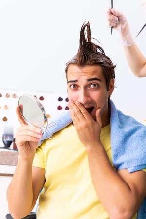Woman hairdresser applying dye to man hair Stok Fotoğraf
