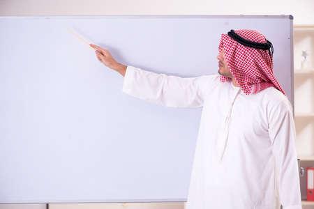 Arab teacher in front of whiteboard Imagens