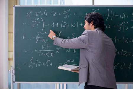 Young handsome math teacher in classroom Archivio Fotografico