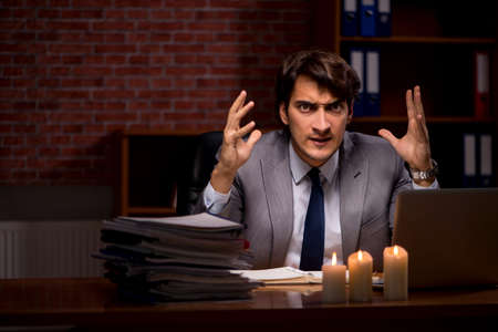 Businessman working late in office with candle light