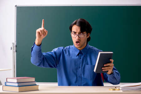 Young male teacher in front of chalkboard Imagens