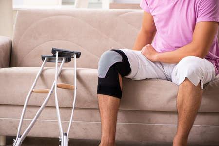 Joven con rodilla lesionada recuperándose en casa Foto de archivo