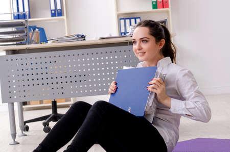 Female employee doing sport exercises in the office