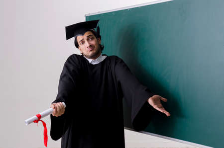 Graduate student in front of green board Stock Photo