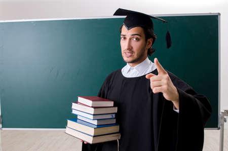 Graduate student in front of green board Archivio Fotografico - 116600943