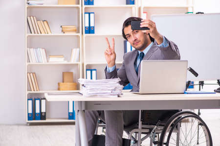Young handsome employee in wheelchair taking selfie at the office