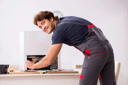 Young handsome contractor repairing fridge Foto de archivo
