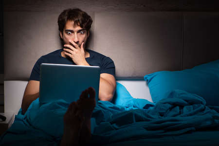 Man working on laptop at night in bed