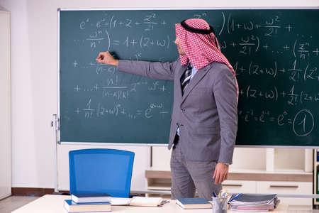 Arab teacher wearing suit in front of chalkboard