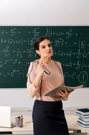 Female teacher standing in front of chalkboard