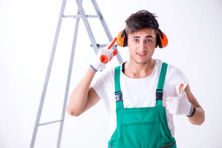 Young worker with earmuffs in noise cancelling concept