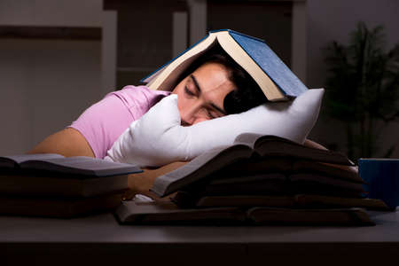 Male handsome student preparing for exams late at home Stock Photo