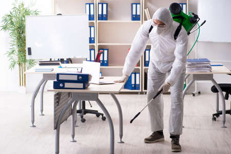 Profesjonalny wykonawca przeprowadzający kontrolę szkodników w biurze