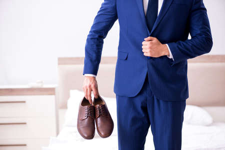 Young handsome businessman choosing shoes at home Stockfoto