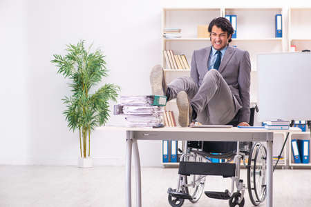 Young handsome employee in wheelchair at the office Imagens